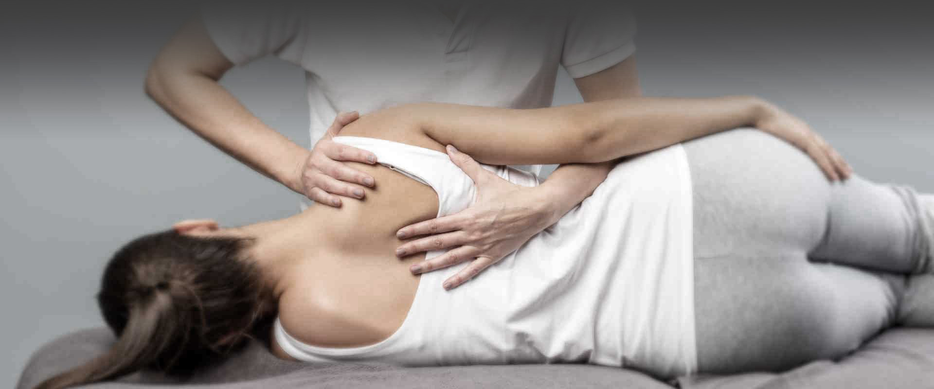 Woman therapist treating female patient for back pain using manual therapy