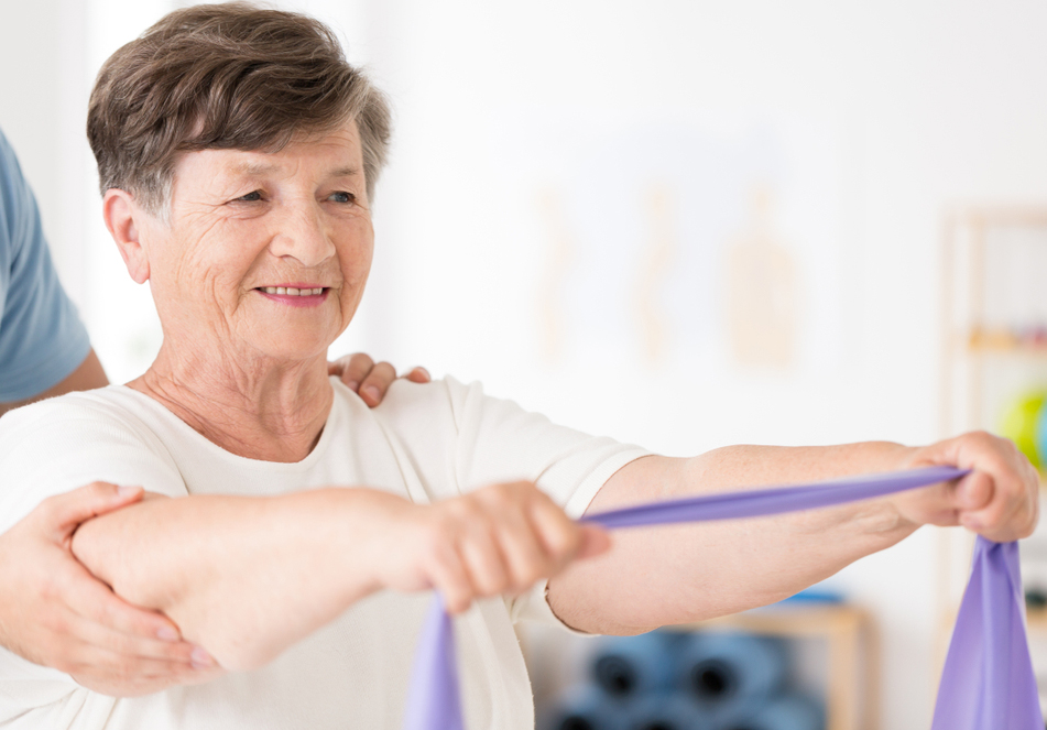Older woman having physiotherapy using a resistance band