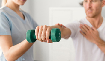 manual therapy for man's arm and shoulder using weights
